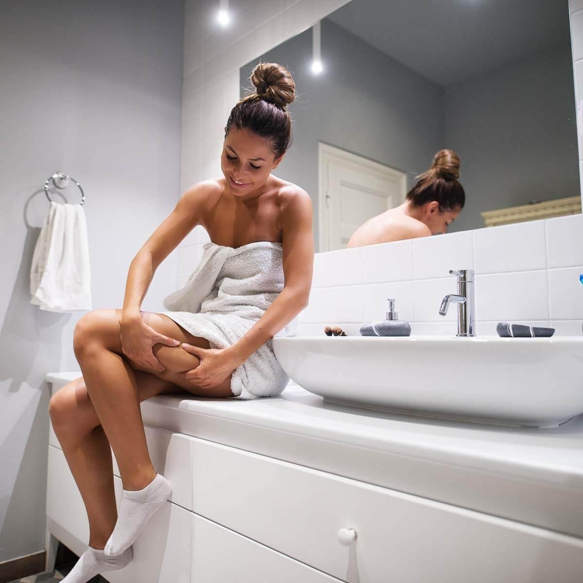Frau schaut auf ihre Beine und möchte Cellulite loswerden