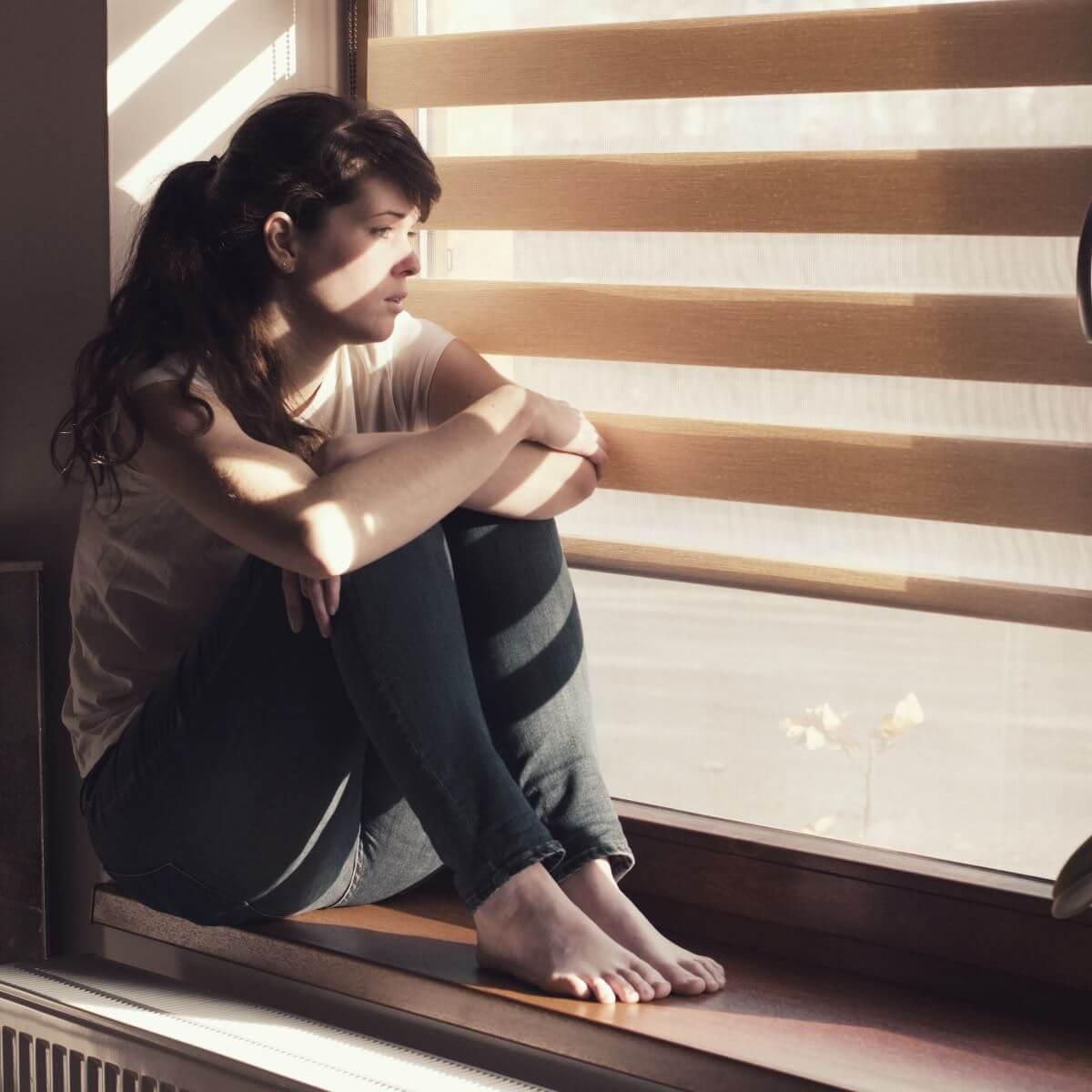 Frau führt Fernbeziehung und schaut aus dem Fenster